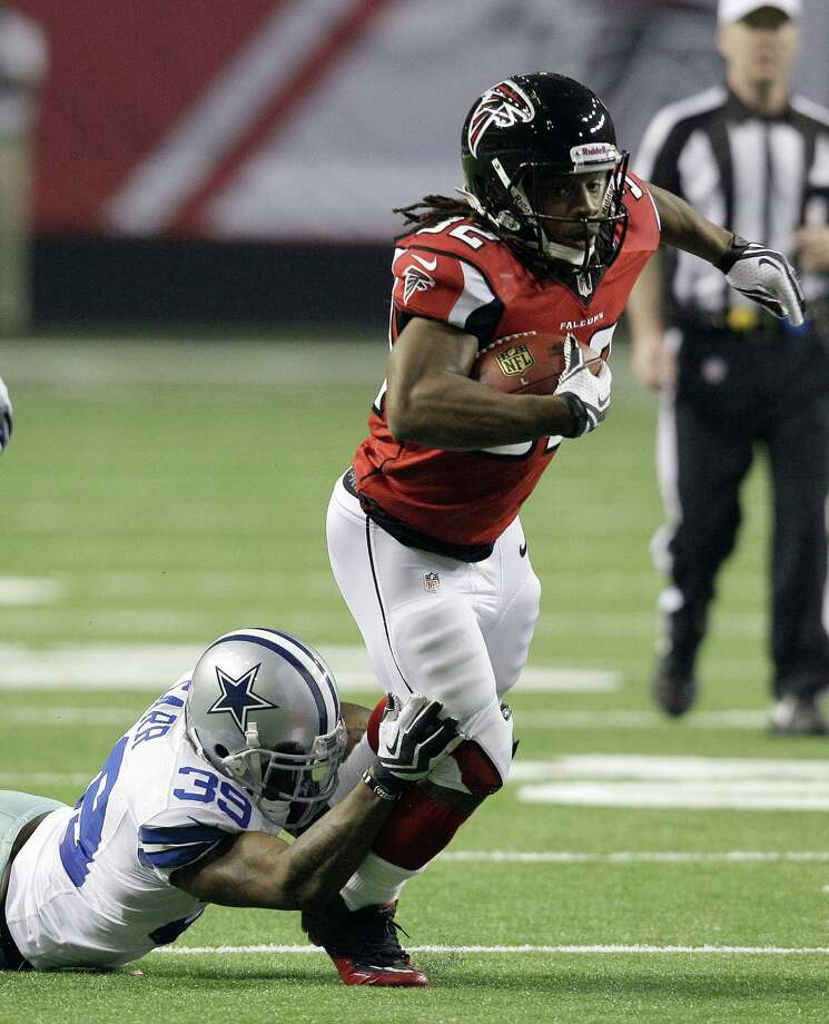 Atlanta Falcons running back Jacquizz Rodgers (32) tries to escape from Dallas Cowboys cornerback Brandon Carr (39)during the second half of an NFL football game Sunday, Nov. 4, 2012, in Atlanta. (AP Photo/Chuck Burton) Photo: Chuck Burton, Associated Press / AP