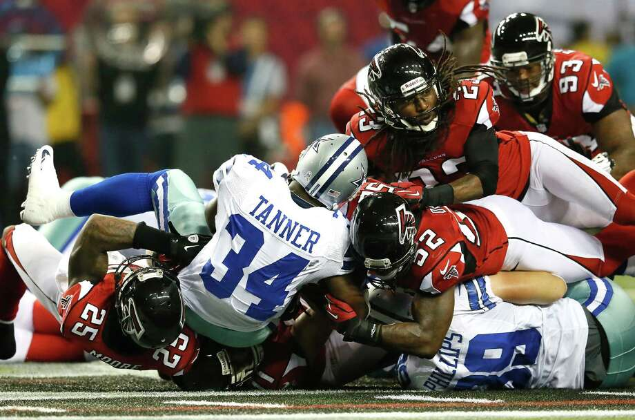 Phillip Tanner #34 of the Dallas Cowboys is stopped short on third down by William Moore #25, Kroy Biermann #71, Akeem Dent #52 and Dunta Robinson #23 of the Atlanta Falcons at Georgia Dome on November 4, 2012 in Atlanta, Georgia. Photo: Kevin C. Cox, Getty Images / 2012 Getty Images