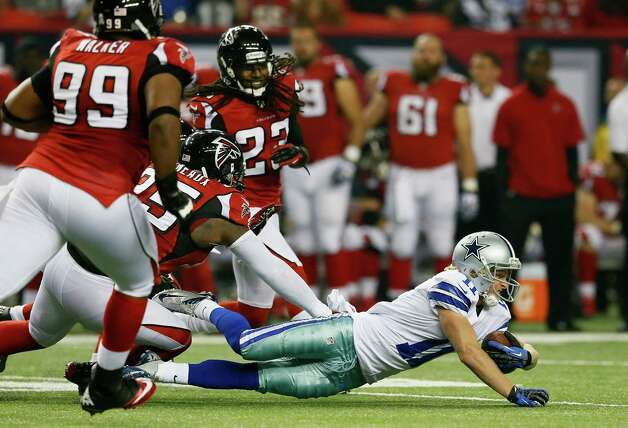 Cole Beasley #11 of the Dallas Cowboys dives for extra yardage against Jonathan Babineaux #95 and Dunta Robinson #23 of the Atlanta Falcons at Georgia Dome on November 4, 2012 in Atlanta, Georgia. Photo: Kevin C. Cox, Getty Images / 2012 Getty Images