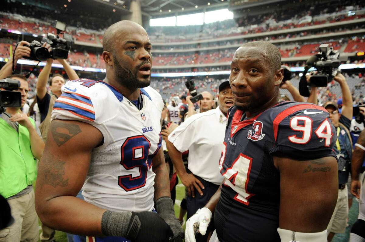Buffalo Bills defensive end and former Houston Texan Mario Williams, right, meets with Houston Texans' Antonio Smith after an NFL football game Sunday, Nov. 4, 2012, in Houston. The Texans won 21-9. (AP Photo/Dave Einsel)