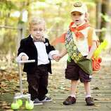 "FINALIST! Sent to us by Rachel S., who says her 3-year-old and 1-year-old are obsessed with the movie ""Up."" As much as I like these amazing Russell and Mr. Fredrickson costumes, I love the fact that the kids are holding hands. Cue the Michael Giacchino score ..."
