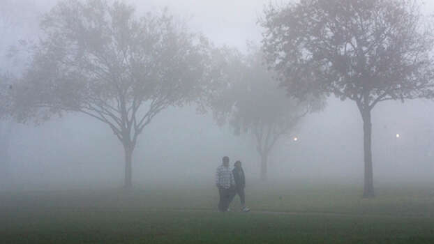Fog hangs as patrons walk through Monte Beach Park Monday, Nov. 5, 2012, in Houston. Photo: Cody Duty, . / © 2012 Houston Chronicle