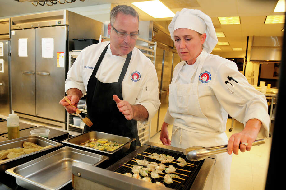 Chef David Berg, left, and student Shannon Bragg team up on grilled shrimp during an International Cuisine class at Culinary Institute LeNotre in Houston. / Greg Krenek