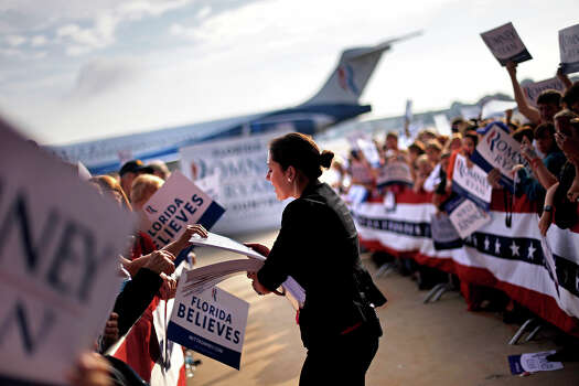 A campaign worker hands out signs to crowd members before Republican presidential candidate, former Massachusetts Gov. Mitt Romney arrives to speak at a campaign event at the Orlando Sanford International Airport, Monday, Nov. 5, 2012, in Sanford, Fla. Photo: AP