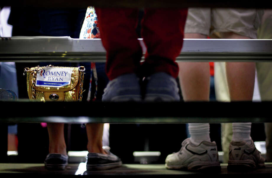 A purse with a Romney-Ryan sticker sits next to suppoters on a bleacher as Republican presidential candidate, former Massachusetts Gov. Mitt Romney spoke at a campaign event at the Orlando Sanford International Airport, Monday, Nov. 5, 2012, in Sanford, Fla. Photo: AP