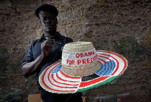 """Street sign maker Salmon Jackoyo, 32, puts the finishing touches to a hat painted with the flags of the USA and Kenya and reading """"Obama for President"""", on the side of the road in downtown Kisumu, western Kenya Monday, Nov. 5, 2012. Many Kenyans consider President Barack Obama, the son of a white mother from Kansas and a black father from Kenya, as one of their own. Photo: AP"""