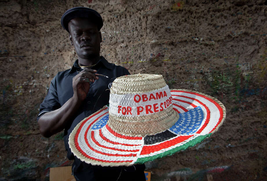 "Street sign maker Salmon Jackoyo, 32, puts the finishing touches to a hat painted with the flags of the USA and Kenya and reading ""Obama for President"", on the side of the road in downtown Kisumu, western Kenya Monday, Nov. 5, 2012. Many Kenyans consider President Barack Obama, the son of a white mother from Kansas and a black father from Kenya, as one of their own. Photo: AP"