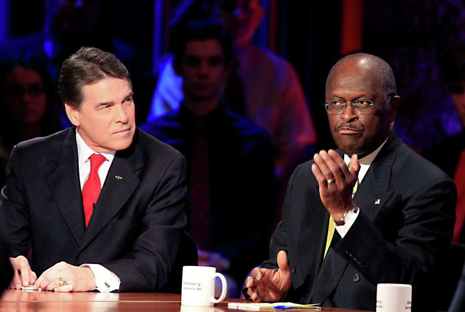 Herman Cain speaks while Rick Perry during a presidential debate sponsored by Bloomberg and The Washington Post held at Dartmouth College in Hanover, N.H., on Tuesday, Oct. 11, 2011. Photo: Andrew Harrer, Bloomberg / © 2011 Bloomberg Finance LP