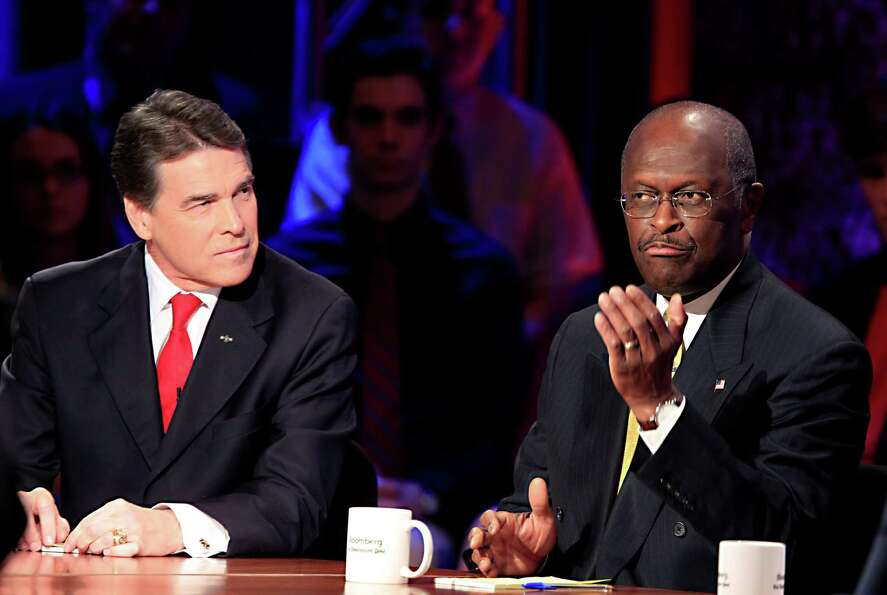 Herman Cain speaks while Rick Perry during a presidential debate sponsored by Bloomberg and The Wash