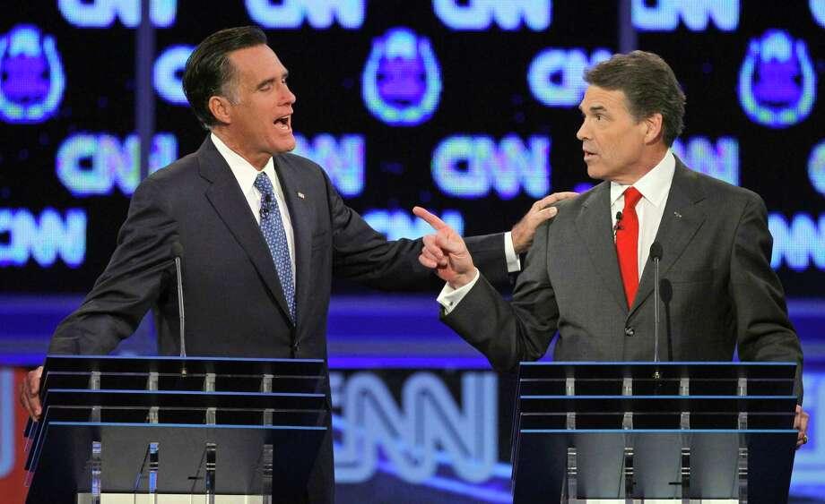 Mitt Romney and Rick Perry speak during a Republican presidential debate in Las Vegas. Photo: Chris Carlson, Associated Press / AP2011