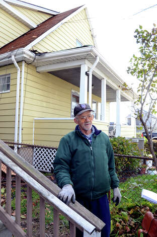 Hector Guzman stands in front of his home on Manor St. in the South end of Stamford on Saturday, Nov. 3, 2012. Guzman's roof was damaged during Hurricane Sandy. Guzman, who does not have homeowners insurance, estimates the roof will cost $10,000. Photo: Amy Mortensen / Connecticut Post Freelance