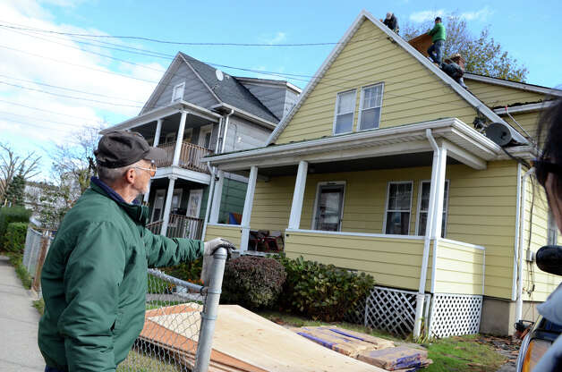 Hector Guzman watches as workers replace the roof of his Manor St. home in the South end of Stamford on Saturday, Nov. 3, 2012. Guzman's roof was damaged during Hurricane Sandy. Guzman, who does not have homeowners insurance, estimates the roof will cost $10,000. Photo: Amy Mortensen / Connecticut Post Freelance