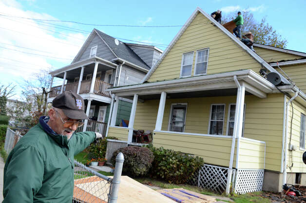 Hector Guzman stands in front of his home on Manor St. in the South end of Stamford as workers replace the roof on Saturday, Nov. 3, 2012. Guzman's roof was damaged during Hurricane Sandy. Guzman, who does not have homeowners insurance, estimates the roof will cost $10,000. Photo: Amy Mortensen / Connecticut Post Freelance