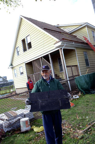 Hector Guzman holds a shingle that fell off of his neighbor's home on Manor St. in the South end of Stamford on Saturday, Nov. 3, 2012. Guzman's roof was damaged during Hurricane Sandy. Photo: Amy Mortensen / Connecticut Post Freelance
