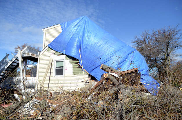 A blue tarp covers the side of a two-story home located at 33 Ponus Ave. in Stamford on Saturday, Nov. 3, 2012. A large tree crashed through the roof during Hurricane Sandy. Photo: Amy Mortensen / Connecticut Post Freelance