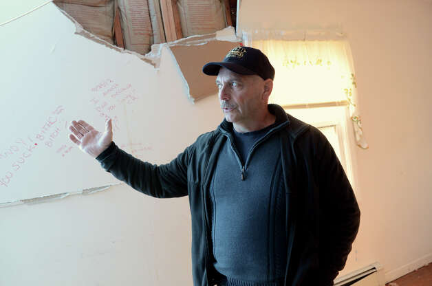 Joe Bonacci, of South Salem, N.Y., surveys the damage to his income property located at 33 Ponus Ave. in Stamford on Saturday, Nov. 3, 2012. A large tree crashed through the roof during Hurricane Sandy. Photo: Amy Mortensen / Connecticut Post Freelance