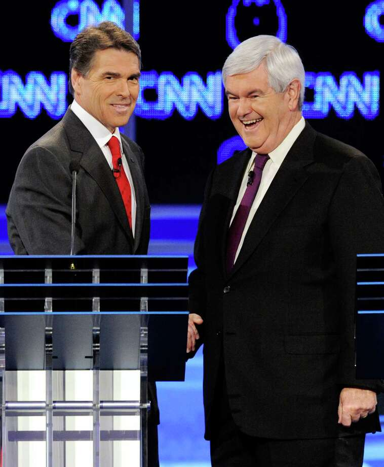 Rick Perry and former Speaker of the House Newt Gingrich shake hands after the Republican presidential debate airing on CNN, October 18, 2011 in Las Vegas. Photo: Ethan Miller, Getty / 2011 Getty Images