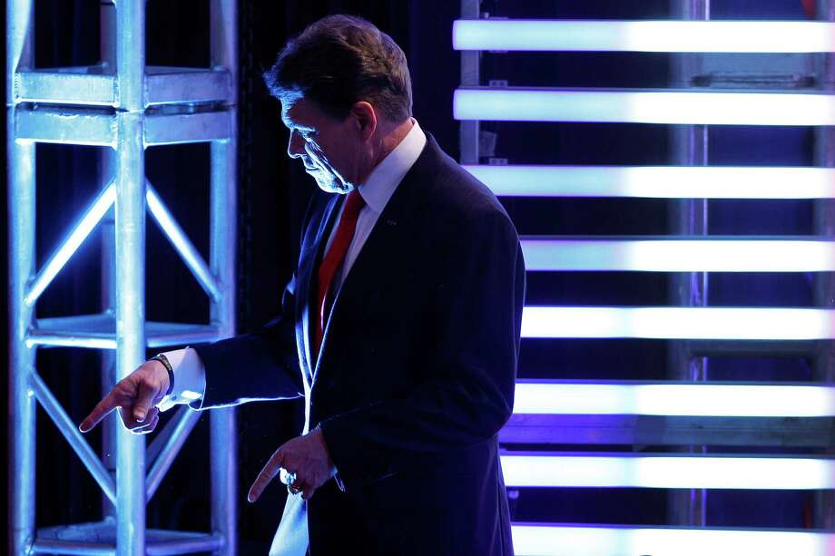 Rick Perry points to a member of the audience during a break in the Republican presidential candidate debate at Saint Anselm College in Manchester, N.H., Saturday, Jan. 7, 2012. Photo: Elise Amendola, Associated Press / AP