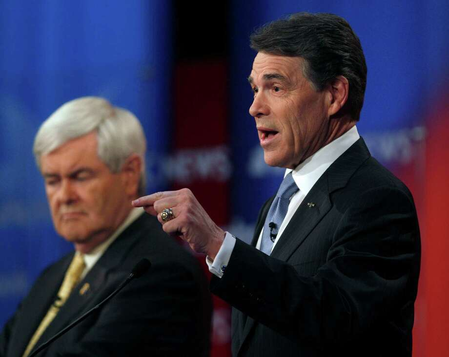 Rick Perry answers a question as Newt Gingrich listens in the background during a Republican presidential candidate debate at the Capitol Center for the Arts in Concord, N.H., Sunday, Jan. 8, 2012. Photo: Charles Krupa, Associated Press / AP