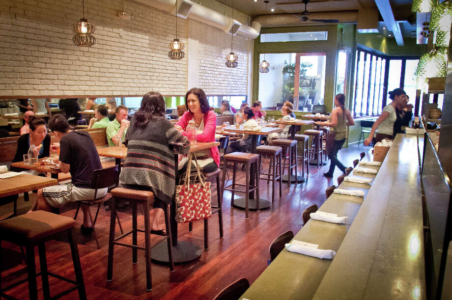 """... Diners walk down a long hall-like passage with windows that wrap around to Ninth Avenue. They can be opened on warmer days to bring in an urban feel. When they're closed, the open kitchen and bar, with green glass globe lights dangling from the ceiling, add excitement."" Photo: John Storey, Special To The Chronicle / John Storey"