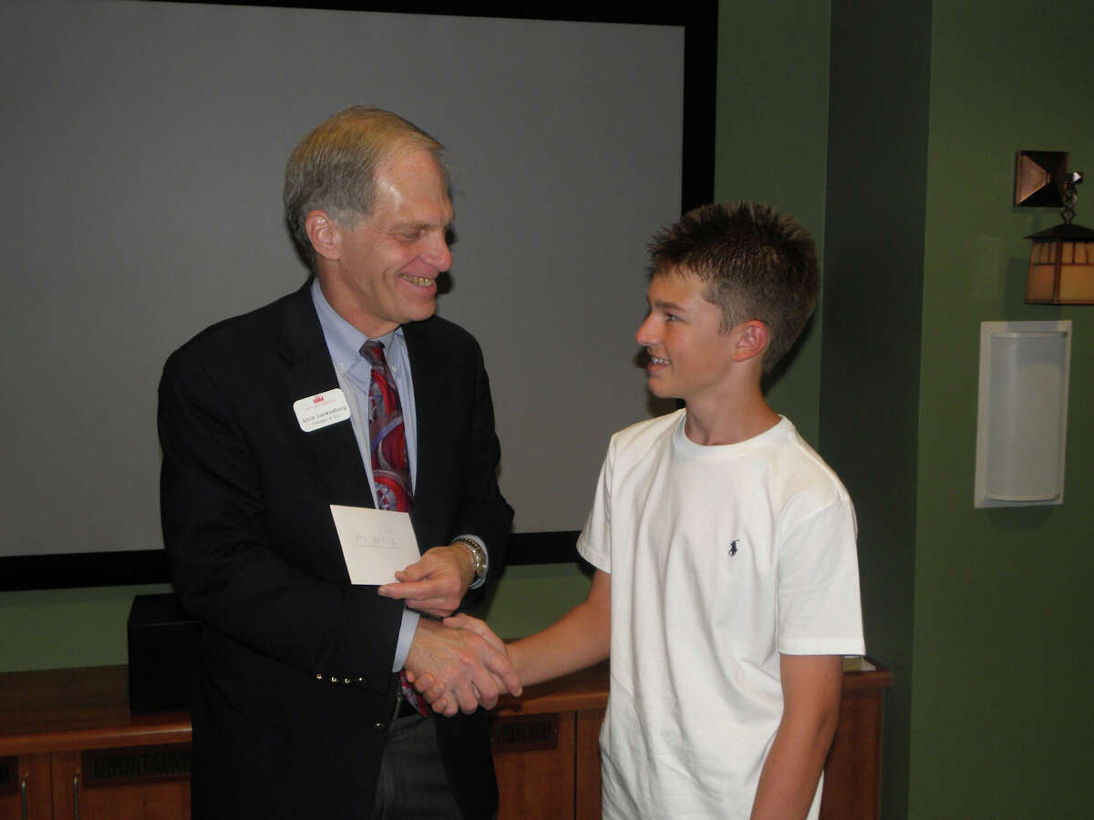 Morningside Ministries President/Chief Executive Officer Alvin Loewenberg accepts a donation from Keystone School student Evan Meade.