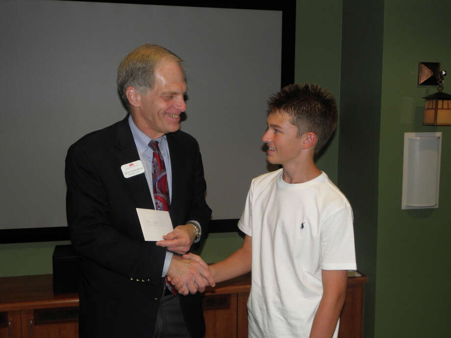 Morningside Ministries President/Chief Executive Officer Alvin Loewenberg accepts a donation from Keystone School student Evan Meade. Photo: Courtesy Photo