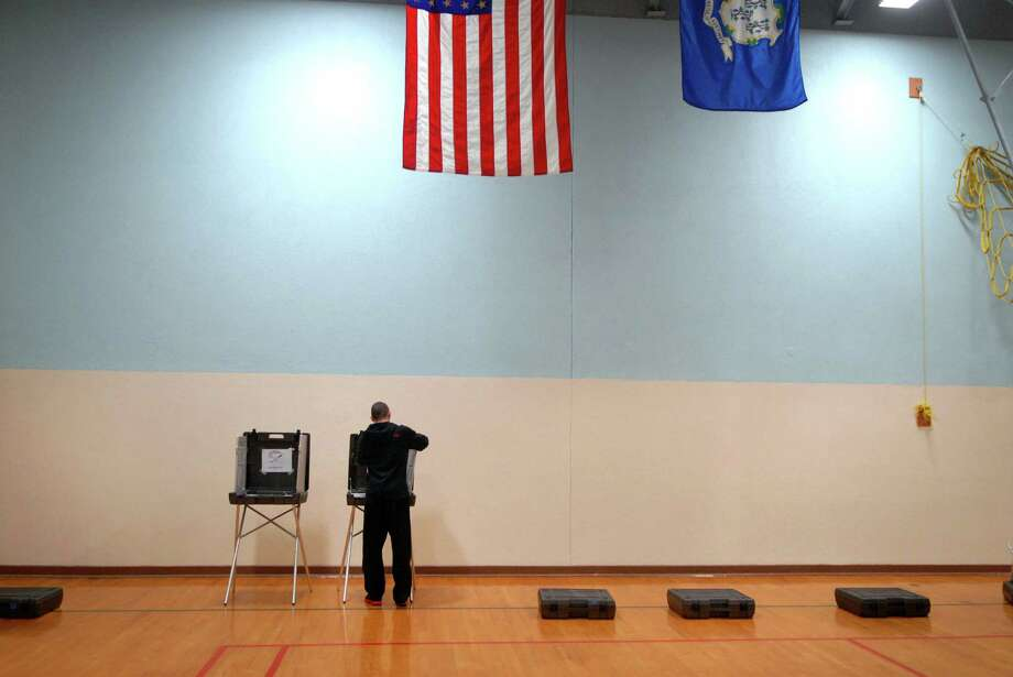 Paul Karwoski sets up voting machines at Davenport Ridge Elementary School in Stamford, Conn. on Monday November 5, 2012 for Tuesday's election. Photo: Dru Nadler / Stamford Advocate Freelance