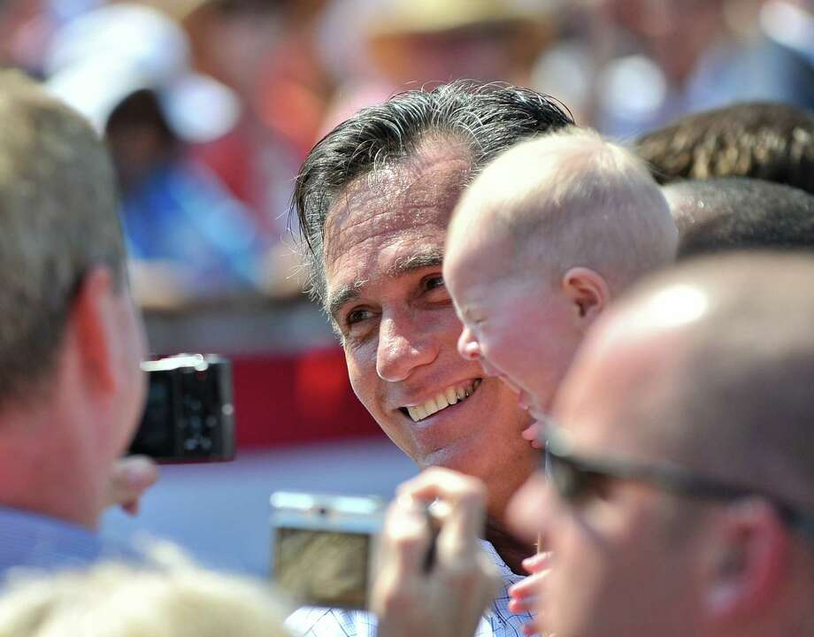 US Republican presidential candidate Mitt Romney holds a crying baby after speaking at a campaign rally in Fairfax, Virginia, on September 13, 2012. (AFP PHOTO/Nicholas Kamm/GettyImages) Photo: NICHOLAS KAMM, AFP/Getty Images / AFP