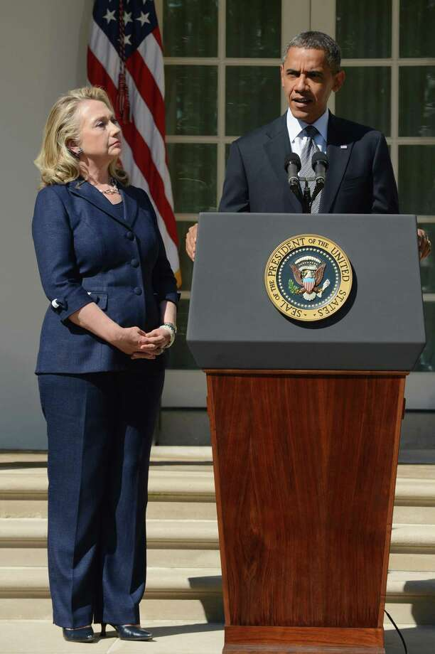 President Barack Obama delivers remarks beside Secretary of State Hillary Clinton, left, on the killing of US ambassador to Libya, Christopher Stevens, and three embassy staff, Wednesday, September 12, 2012, in the Rose Garden of the White House in Washington, D.C. Gunmen attacked the US consulate in Benghazi, killing Stevens and three others, late September 11, 2012, while another assault took place on the US embassy in Cairo. (Pool photo by Michael Reynolds/EPA via Abaca Press/MCT) Photo: Michael Reynolds, McClatchy-Tribune News Service / Abaca Press