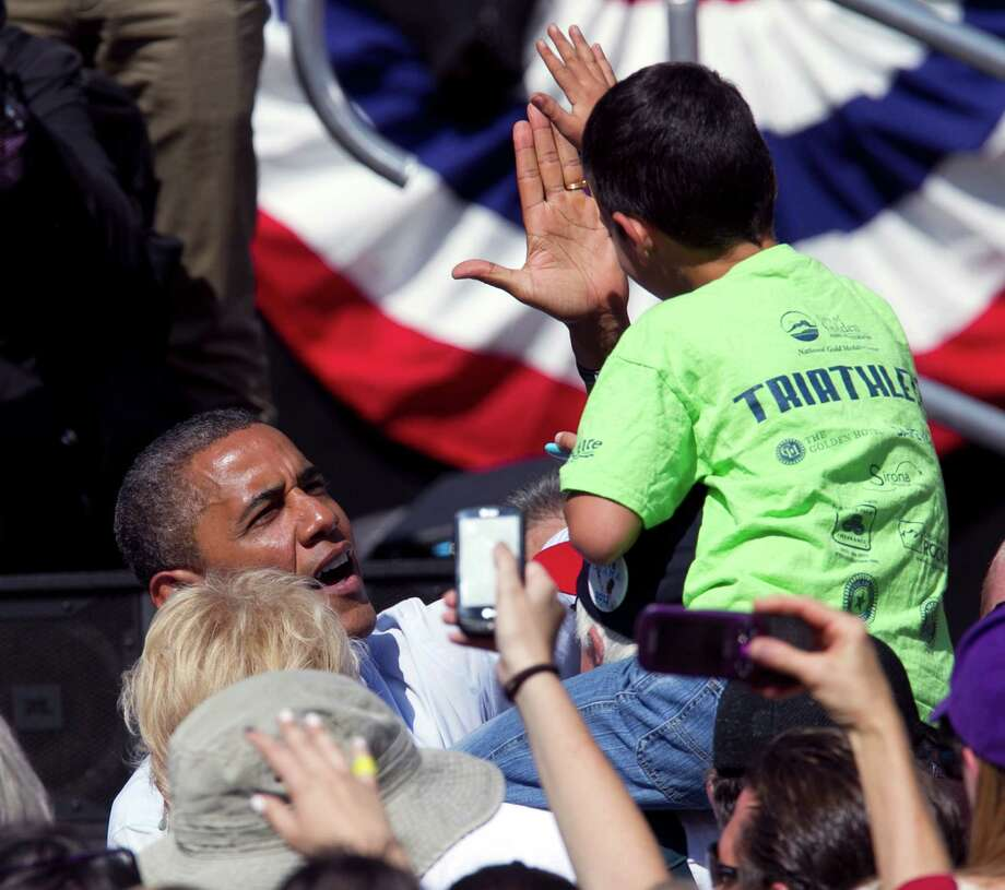 President Barack Obama exchanges a high-five with a youngster after speaking at a campaign rally in Golden, Colo., on Thursday, Sept. 13, 2012. (AP Photo/Ed Andrieski) Photo: Ed Andrieski, Associated Press / AP