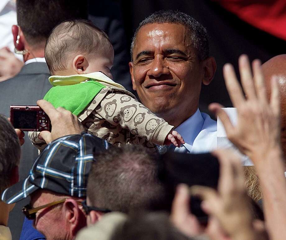 President Barack Obama holds a young child as he greets supporters after speaking at a campaign rally in Golden, Colo., Thursday, Sept. 13, 2012. (AP Photo/Ed Andrieski) Photo: Ed Andrieski, Associated Press / AP