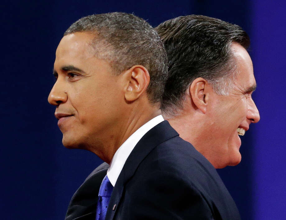 In this Oct. 22, 2012 file photo, Mitt Romney and President Obama walk past each other on stage at the end of the last debate at Lynn University in Boca Raton, Fla. Photo: AP