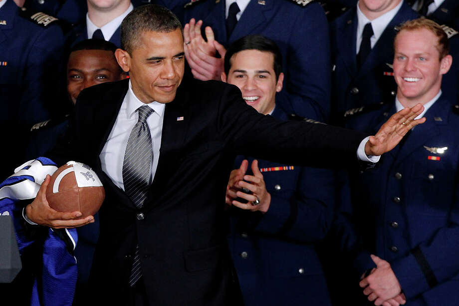 In this April 23, 2012 file photo, President Obama strikes the Heisman pose after he awarded the Commander-in-Chief Trophy to the Air Force Academy football team in the East Room of the White House in Washington. Photo: AP