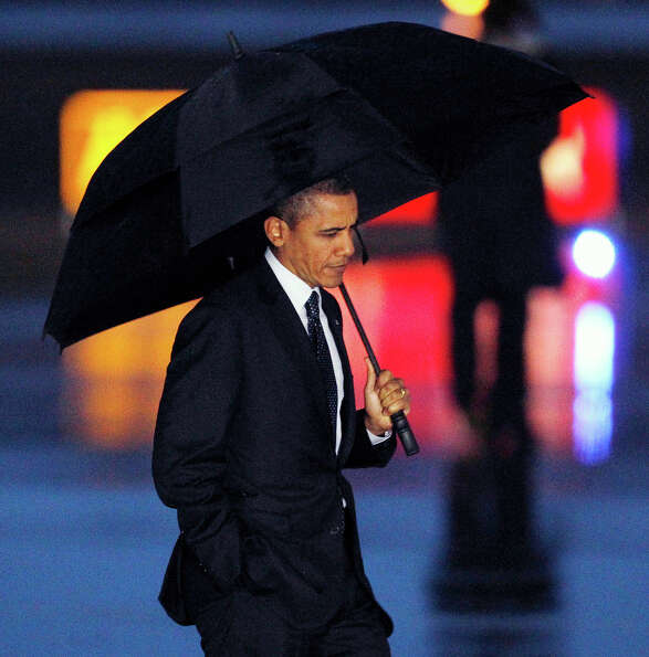 In this Feb. 17, 2012 file photo, President Obama is framed by runway lights as he walks across the