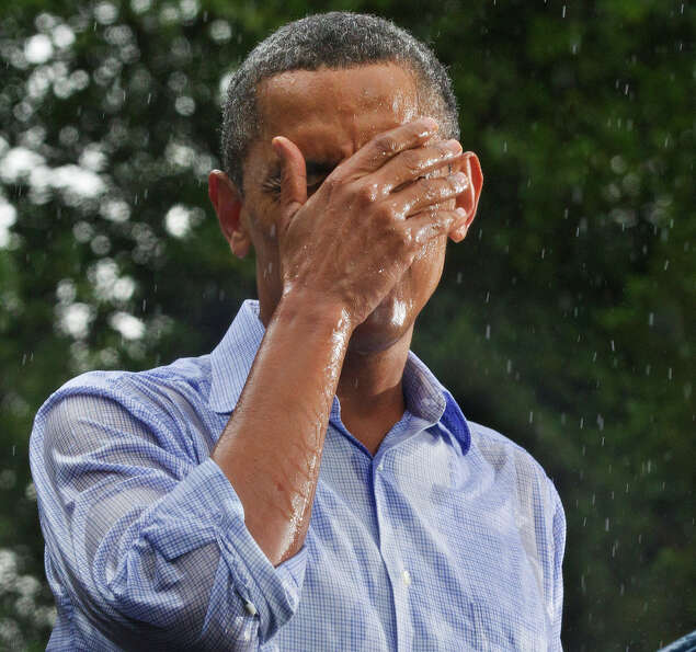 In this July 14, 2012 file photo, President Obama holds a campaign rally despite heavy rain at the h