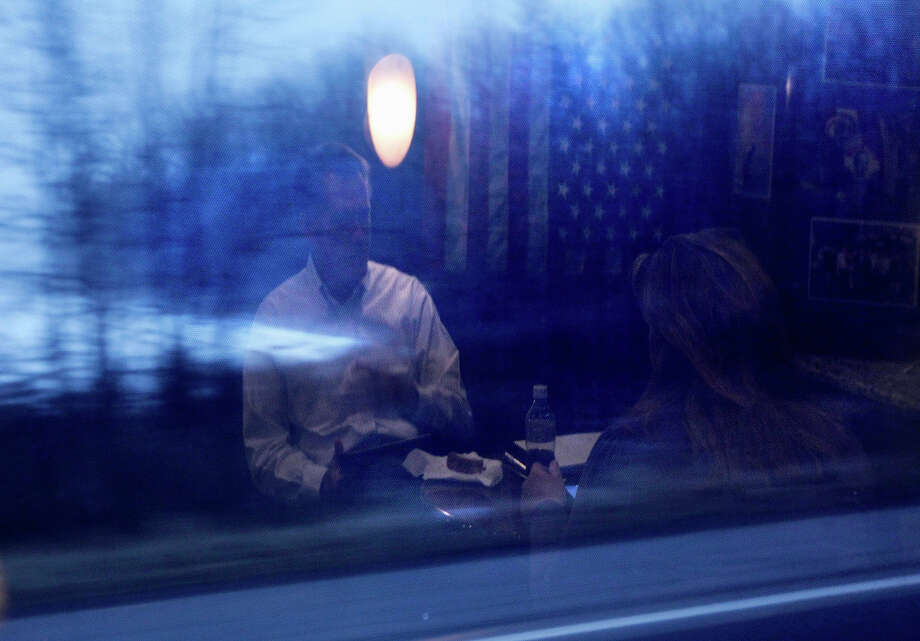 In this Feb. 16, 2012 file photo, Mitt Romney is reflected in a window as he talks with deputy campaign manager Katie Gage on his campaign bus between Monroe, Mich., and Farmington Hills, Mich. Photo: AP
