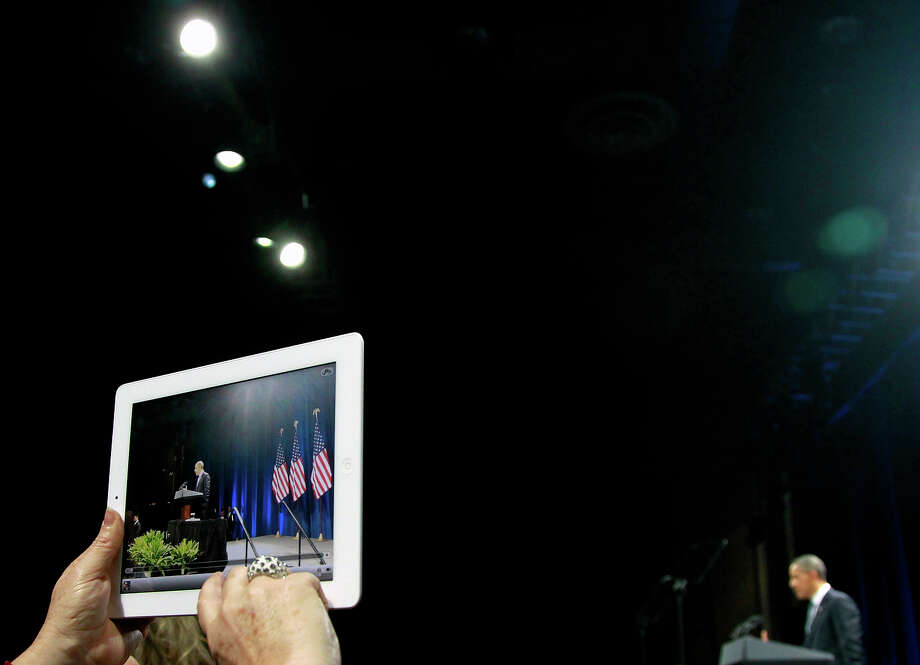 In this Jan. 11, 2012 file photo, an audience member takes a photo of President Obama as he speaks during a campaign event at the University of Illinois in Chicago. Photo: AP
