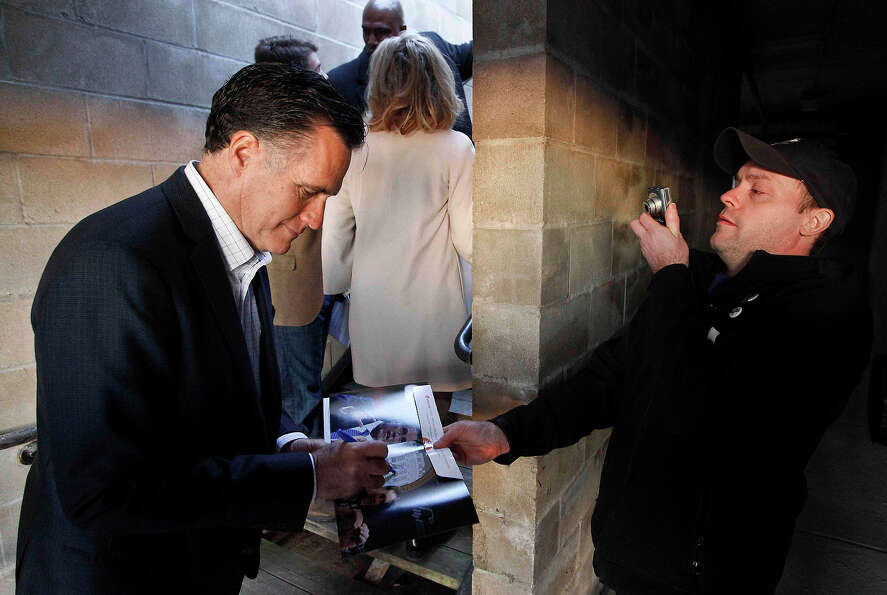 In this Dec. 28, 2011 file photo, Mitt Romney signs an autograph during a campaign stop at Elly's Te