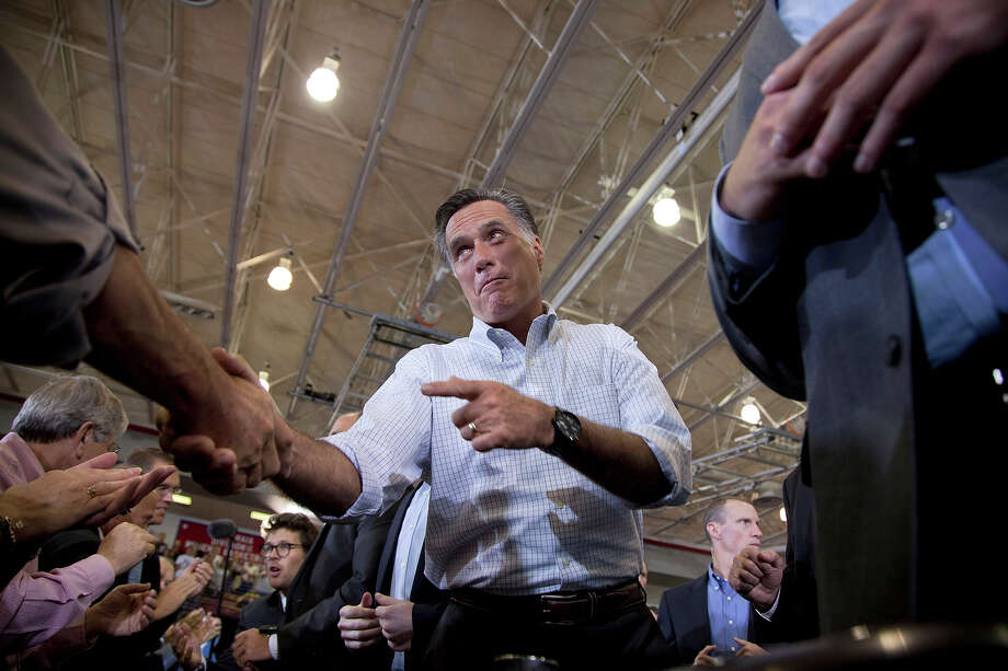 In this Sept. 7, 2012 file photo, Mitt Romney shakes hands during a campaign rally in Orange City, Iowa. Photo: AP