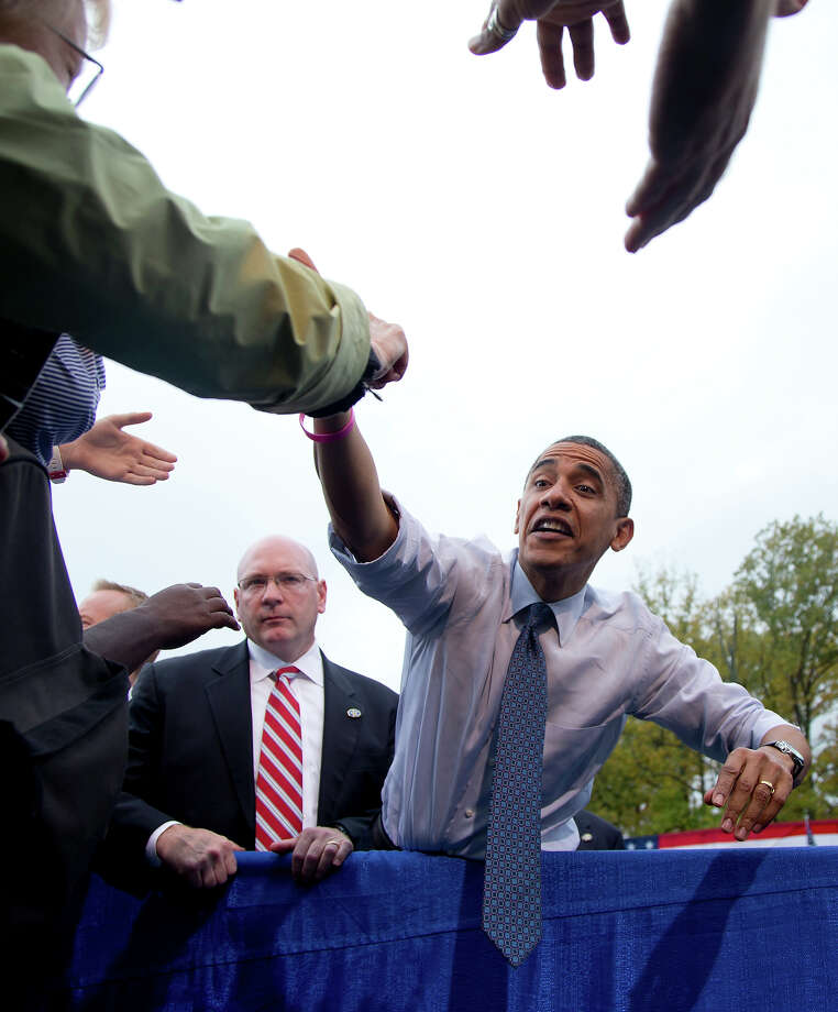 In this Oct. 19, 2012 file photo, President Obama stretches to shakes hands with supporters at a campaign event at George Mason University, in Fairfax, Va. Photo: AP