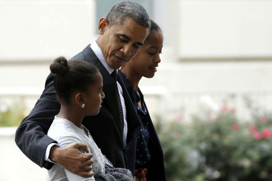 President Barack Obama hugs his daughter Sasha as he walks with Malia as they leave St. John's Episcopal Church to walk across Lafayette Park as they return to the White House in Washington, on Sunday, Oct. 28, 2012.  (Jacquelyn Martin / AP Photo)