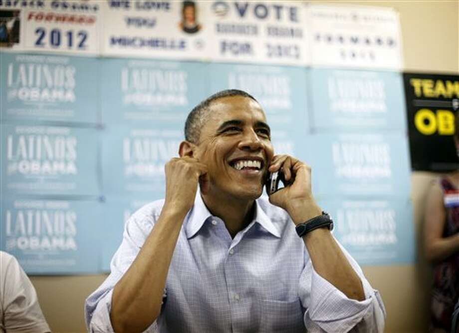 President Barack Obama uses a cell phone to call supporters during a visit to a local campaign office, Monday, Oct. 1, 2012, in Henderson, Nev.  (Pablo Martinez Monsivais / AP Photo) Photo: Pablo Martinez Monsivais, ASSOCIATED PRESS / AP2012