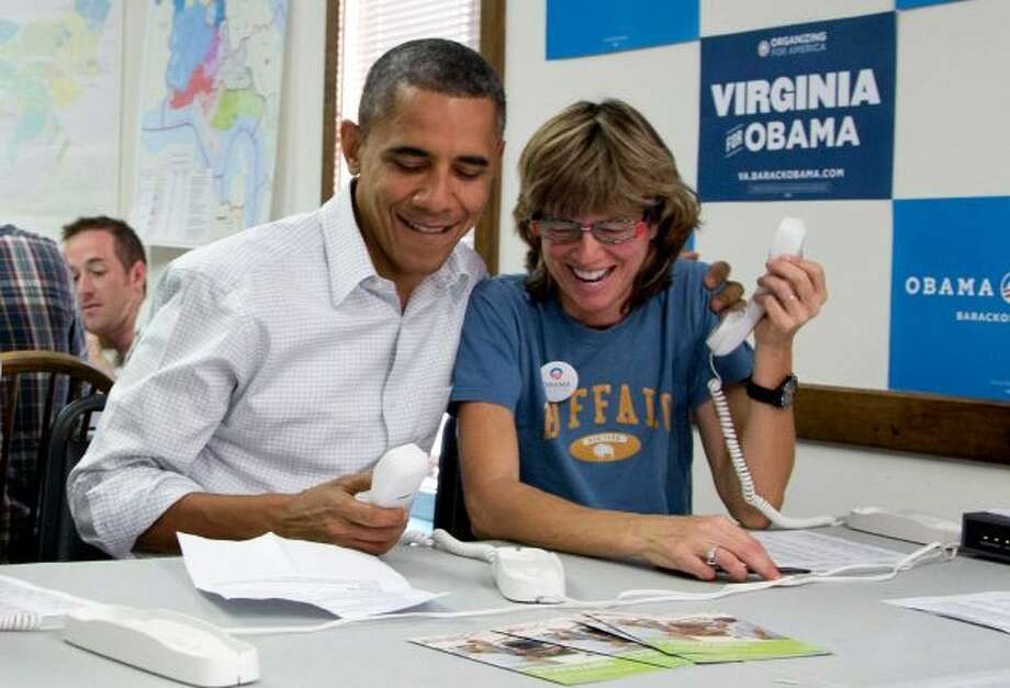 President Barack Obama makes phone calls to volunteers at an Obama campaign office with Suzanne Stern, right, Sunday, Oct. 14, 2012, in Williamsburg, Va.  (Carolyn Kaster / AP Photo)