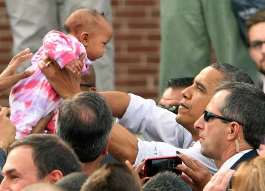 President Barack Obama reaches out to hold a baby at campaign event at Elm Street Middle School, Saturday, Oct. 27, 2012 in Nashua, N.H. (Jim Cole / AP Photo)