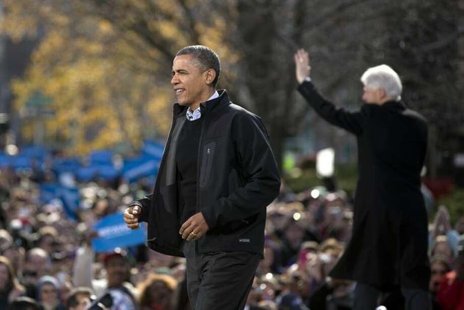 President Barack Obama walks to the podium as former President Bill Clinton waves to the crowd at right during a campaign event in the State Capitol Square, Sunday, Nov. 4 (Carolyn kaster / AP Photo)