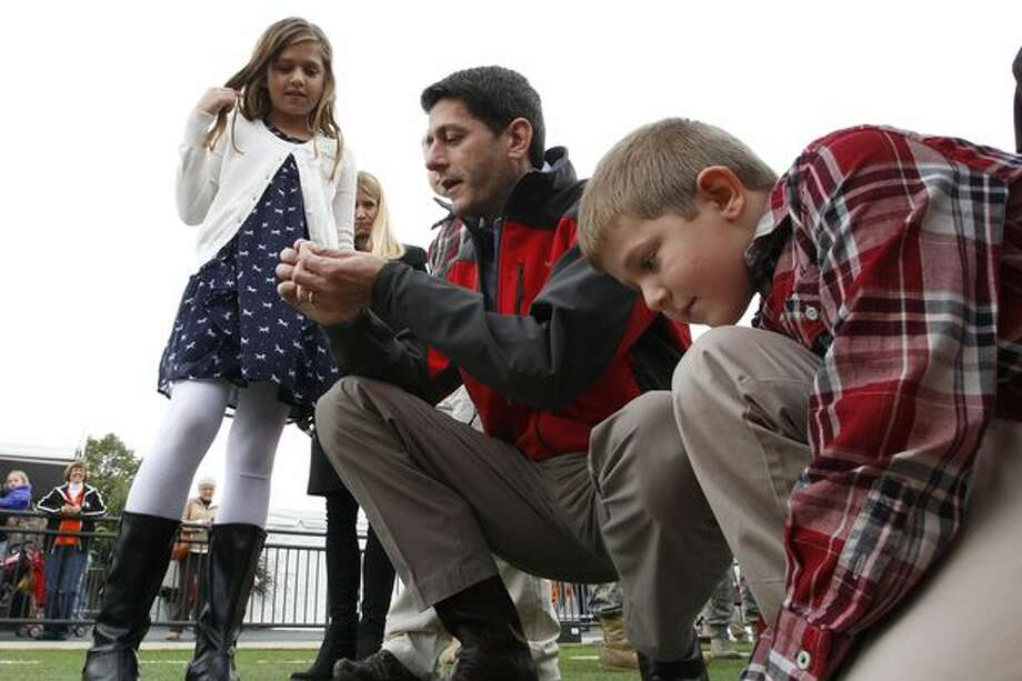 Republican vice presidential candidate, Rep. Paul Ryan, R-Wis., talks to his daughter, Liza, and son, Sam, about the stadium astroturf at a Bowling Green State University and Miami University of Ohio football game, Saturday, Oct. 13, 2012 in Bowling Green, Ohio. (Mary Altaffer / AP Photo)