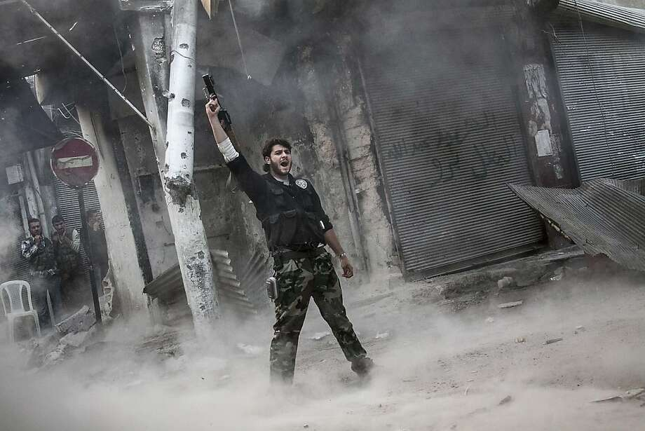 A rebel fighter exultsafter discharging a shoulder-fired missile  at a building where Syrian troops loyal to President Bashar Assad are  hiding during heavy clashes in the Jedida district of Aleppo Photo: Narciso Contreras, Associated Press