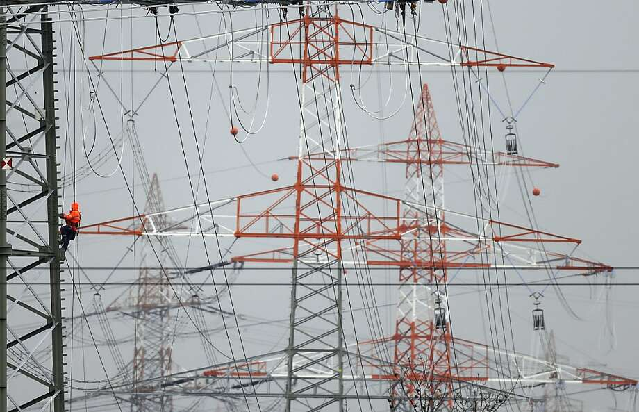You guys threw the 'off' switch, right? A worker climbs a tower holding an array of high-tension power lines in Dortmund, Germany. Photo: Frank Augstein, Associated Press