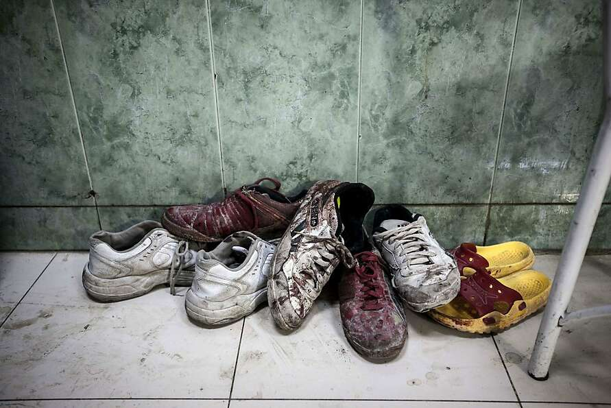 Bloodstained shoes lie at the entrance of the emergency ward of hospital in the Tarik Al-Bab