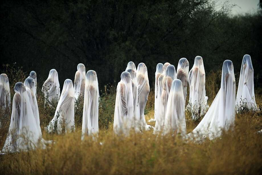 Ghosts of the Day of the Dead:Naked volunteers draped in sheer fabric pose for U.S. photographer and artist Spencer Tunick's group portrait at Los Senderos in Guanajuato state, Mexico. Tunick was in Mexico for one day to photograph a performance commemorating the Day of the Dead. Photo: Alfredo Estrella, AFP/Getty Images